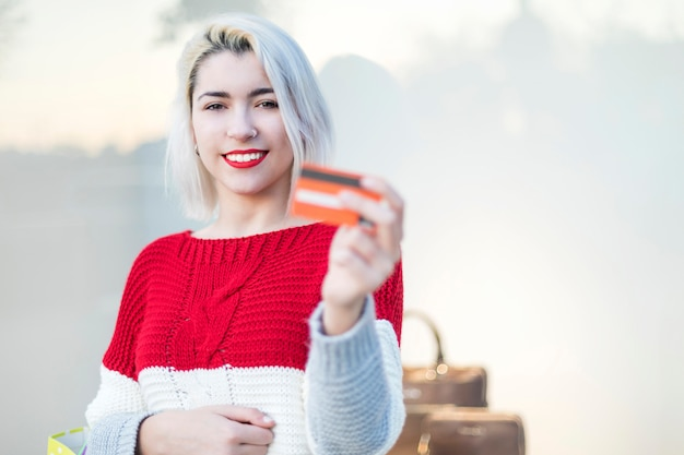 Jonge vrouw in een winkelcentrum terwijl een creditcard Premium Foto