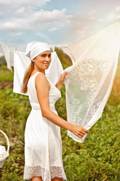 Jonge vrouw in een witte jurk wasgoed buiten ophangen Premium Foto