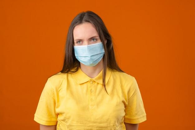 Jonge vrouw in geel poloshirt en medisch beschermend masker dat zich op oranje achtergrond bevindt Gratis Foto