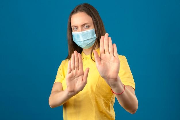 Jonge vrouw in geel poloshirt en medisch beschermend masker die eindegebaar met handen op geïsoleerde blauwe achtergrond maken Gratis Foto