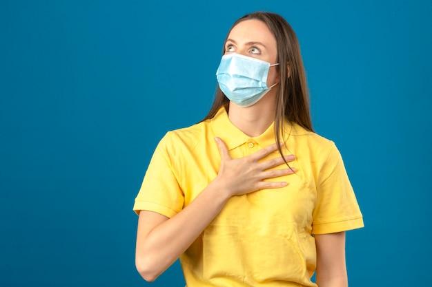 Jonge vrouw in geel poloshirt en medisch beschermend masker die omhooggaand en wat betreft haar borst op blauw geïsoleerde achtergrond kijken Gratis Foto