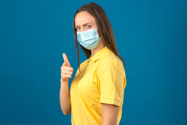 Jonge vrouw in geel poloshirt en medisch beschermend masker die vinger richten aan camera met ernstig gezicht die zich op blauw geïsoleerde achtergrond bevinden Gratis Foto
