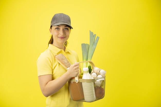 Jonge vrouw in gele uniforme behandelingsmand met voedsel, fruit, groente, melk en eieren Premium Foto