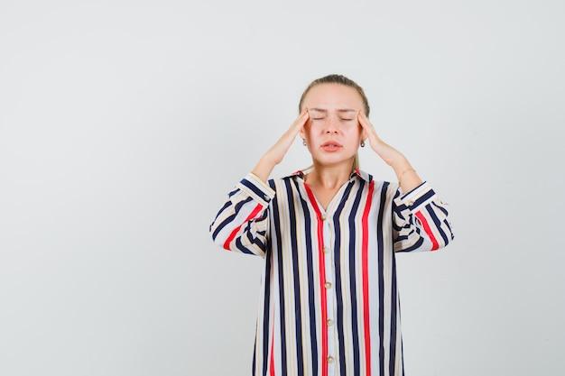Jonge vrouw in gestreepte blouse die haar hoofd bedekt met handen en uitgeput kijkt Gratis Foto
