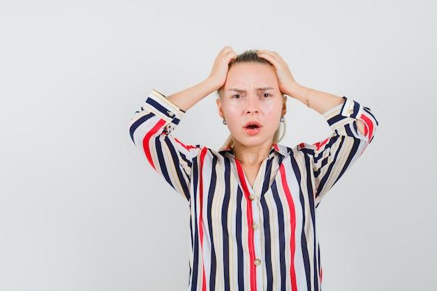 Jonge vrouw in gestreepte blouse die haar hoofd met beide handen behandelt en verrast kijkt Gratis Foto