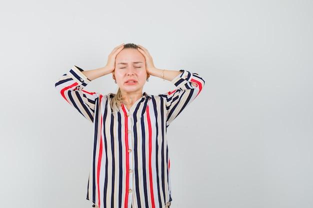 Jonge vrouw in gestreepte blouse die haar hoofd met beide handen behandelt en verward kijkt Gratis Foto