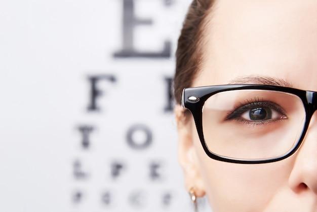 Jonge vrouw in glazen op de achtergrond van een lijst voor visie. Premium Foto