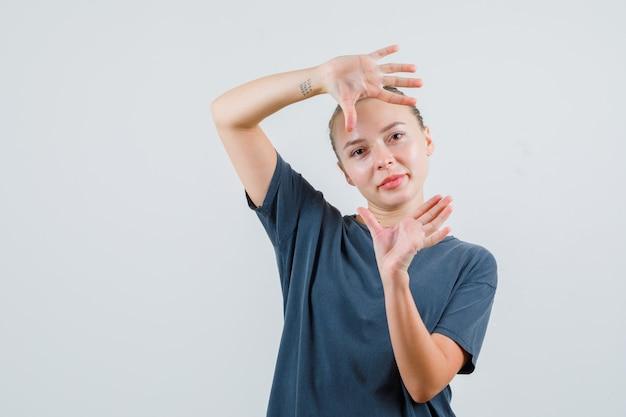 Jonge vrouw in grijs t-shirt die palmen opheft zoals het nemen van foto en dartel kijkt Gratis Foto