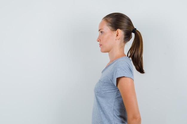 Jonge vrouw in grijs t-shirt hand in hand op haar rug en op zoek gericht. Gratis Foto