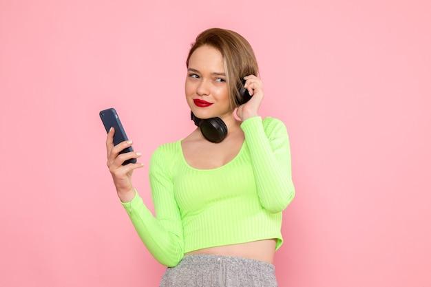 Jonge vrouw in groen shirt en grijze rok met behulp van een telefoon en luisteren naar muziek Gratis Foto