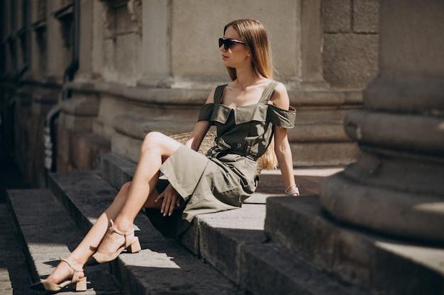 Jonge vrouw in groene jurk zittend op de trappen van een oud gebouw Gratis Foto