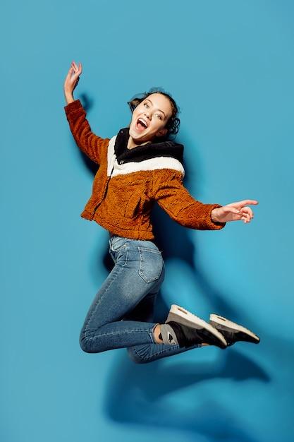 Jonge vrouw in het toevallige springen in lucht over blauwe achtergrond Premium Foto