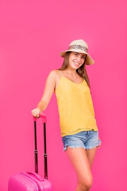 Jonge vrouw in hoed die en koffer bevindt zich houdt Gratis Foto