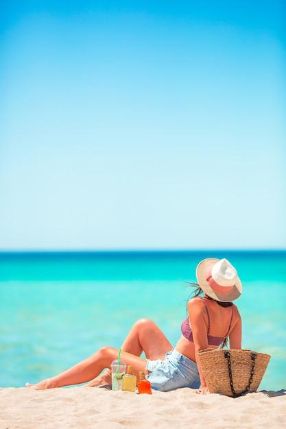 Jonge vrouw in hoed die op het strand zonnebaadt Premium Foto