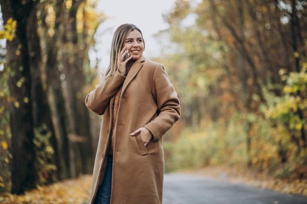 Jonge vrouw in jas die zich op de weg in een de herfstpark bevindt Gratis Foto