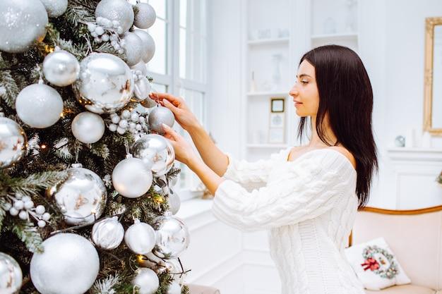 Jonge vrouw in jurk naast kerstboom Premium Foto