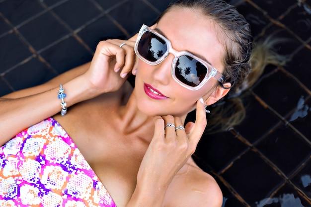 Jonge vrouw in lichte bikini en stijlvolle zonnebril, lag en ontspannen bij creatieve zwarte zwembad, geniet van haar vakantie. Gratis Foto