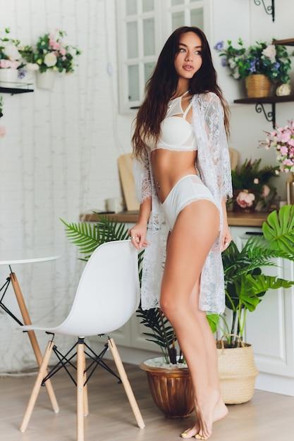 Jonge vrouw in lingerie in haar keuken Premium Foto