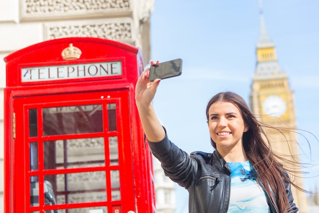 Jonge vrouw in londen met telefooncel en de big ben Premium Foto
