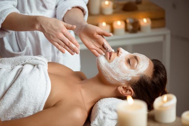 Jonge vrouw in masker voor gezicht ontspannen in de spa salon. Gratis Foto
