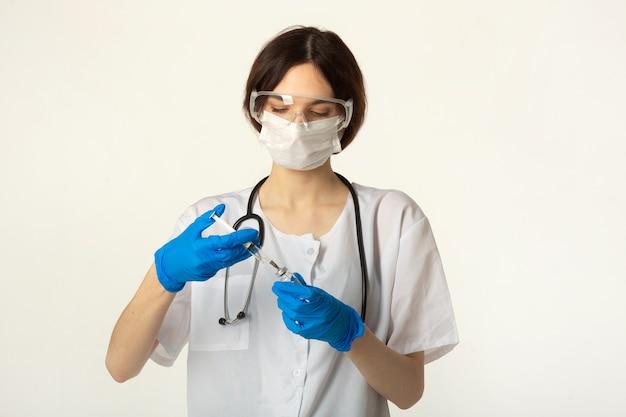 Jonge vrouw in medische kleding op een witte achtergrond met een vaccin en een spuit Premium Foto