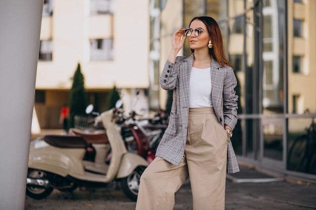 Jonge vrouw in pak die zich door de autoped bevinden Gratis Foto