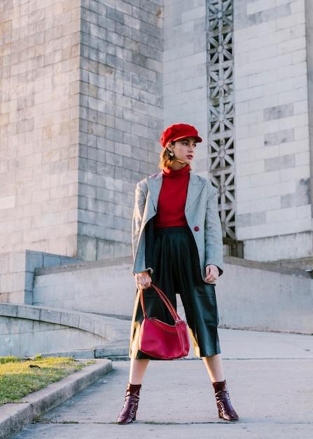 Jonge vrouw in rode glb-holdingszak die zich voor de bouw bevindt Gratis Foto