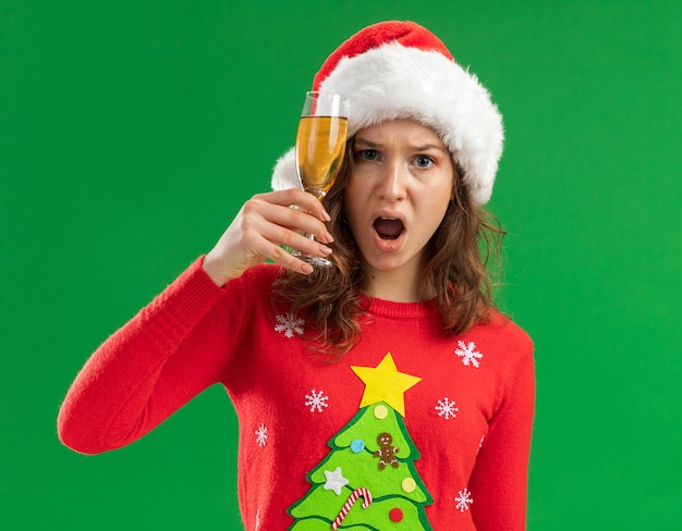 Jonge vrouw in rode kerst trui en kerstmuts bedrijf glas champagne kijken camera geïrriteerd en geïrriteerd staande over groene achtergrond Gratis Foto