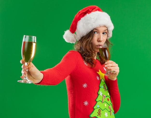 Jonge vrouw in rode kerst trui en kerstmuts met twee glazen champagne drinken op zoek zelfverzekerd staande over groene achtergrond Gratis Foto