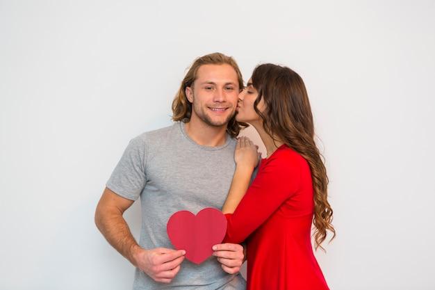Jonge vrouw in rode kleding die haar vriend kussen die het rode document van de hartvorm houden tegen witte achtergrond Gratis Foto