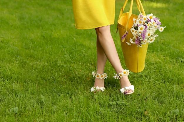 Jonge vrouw in sandalen met madeliefjes aan haar voeten en bloemen in een gele zak lopen. Premium Foto