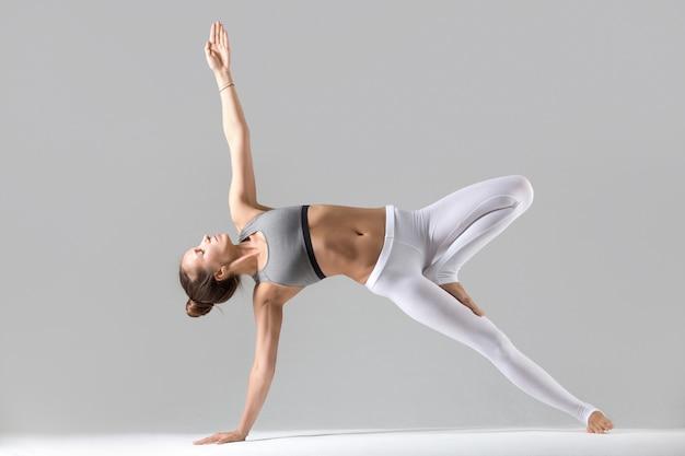 Jonge vrouw in side plank poseren, grijze studio achtergrond Gratis Foto