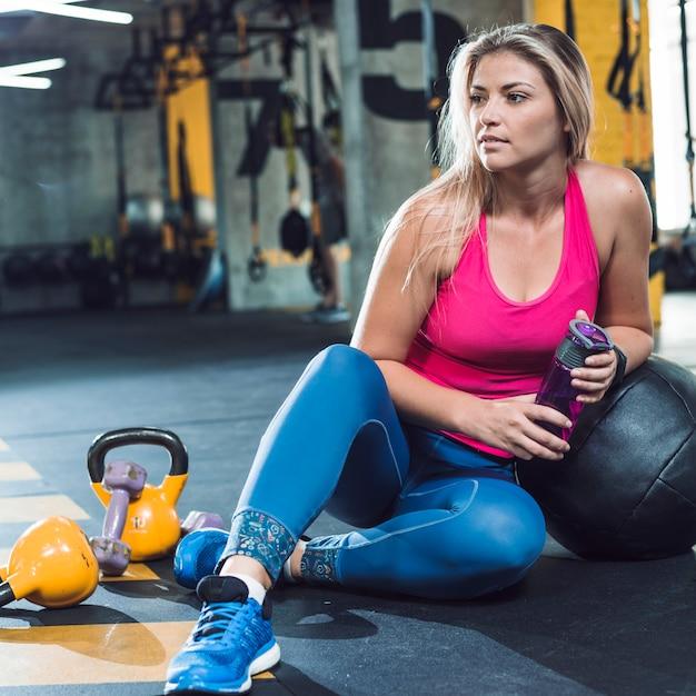 Jonge vrouw in sportkleding zittend op de vloer Gratis Foto