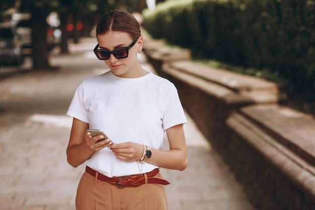 Jonge vrouw in stadscentrum die op telefoon spreekt Gratis Foto