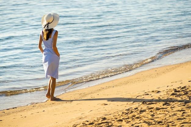 Jonge vrouw in strohoed en een kleding die alleen op leeg zandstrand op overzeese kust lopen Premium Foto