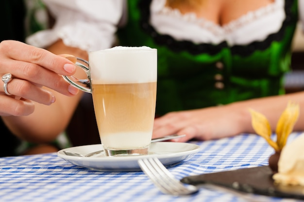 Jonge vrouw in traditionele beierse klederdracht in restaurant of pub Premium Foto