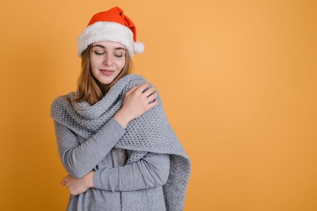 Jonge vrouw in warme trui en kerstmuts op oranje achtergrond Premium Foto