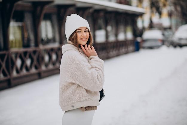 Jonge vrouw in winteroutfit buiten de straat Gratis Foto