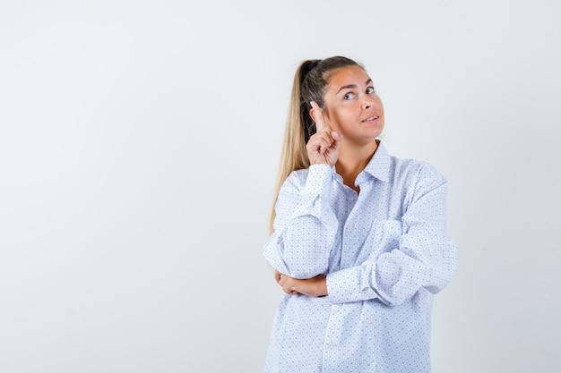 Jonge vrouw in wit overhemd dat met wijsvinger naar rechts richt en er verstandig uitziet Gratis Foto