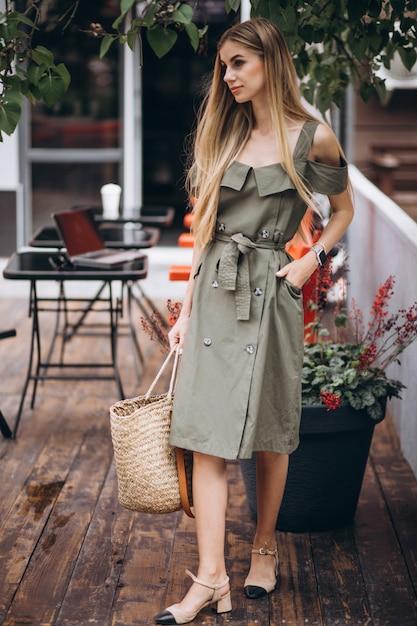 Jonge vrouw in zomer outfit buiten café Gratis Foto