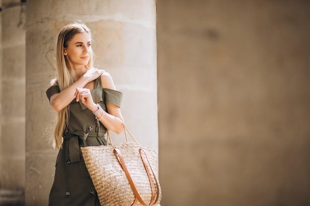 Jonge vrouw in zomer outfit door een oud gebouw Gratis Foto