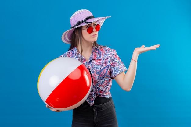 Jonge vrouw in zomerhoed die rode zonnebril draagt die opblaasbare bal houdt die opzij kijkt met fronsend gezicht ontevreden status met opgeheven wapen over blauwe achtergrond Gratis Foto