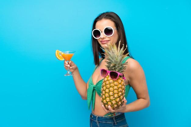Jonge vrouw in zwempak in de zomervakantie met een cocktail Premium Foto