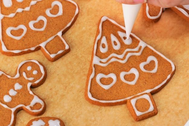 Jonge vrouw is het versieren van christmas gingerbread house koekjes koekje thuis met glazuur topping in suikerglazuur zak, close-up, lifestyle. Premium Foto