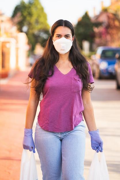 Jonge vrouw keert terug van winkelen met tassen in handen met medische handschoenen en een virusmasker tijdens de coronavirus pandemie in de straat Premium Foto