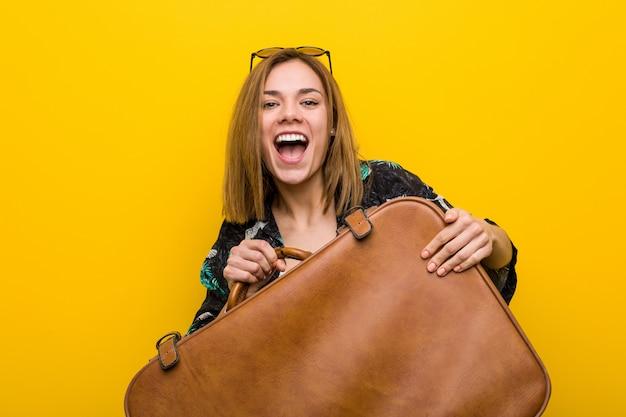 Jonge vrouw klaar om naar vakantie over geel te gaan Premium Foto