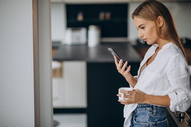 Jonge vrouw koffie drinken in de keuken Gratis Foto