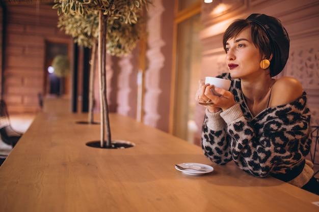 Jonge vrouw koffie drinken in een café Gratis Foto