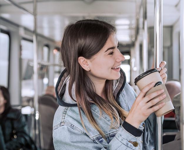 Jonge vrouw koffie drinken in het openbaar vervoer Gratis Foto