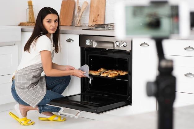 Jonge vrouw koken voor een video Gratis Foto